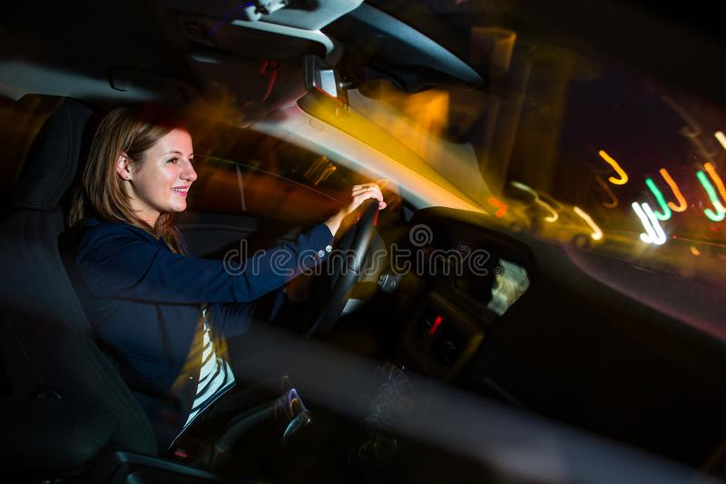 Driving a car at night - pretty, young woman driving her car royalty free stock photography