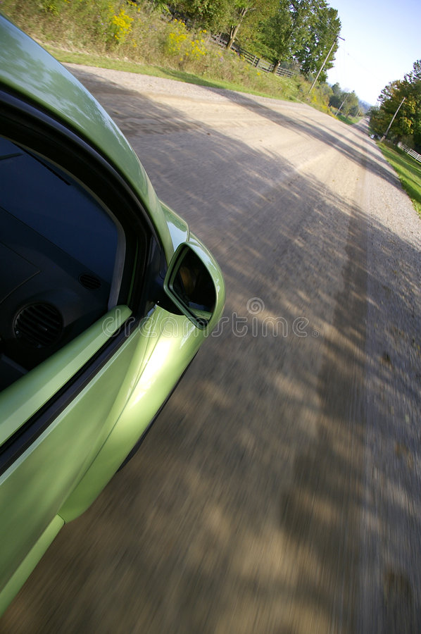 Driving Car on Road. A downward side view of a green car driving along a country road. Side of car, side mirror, side window, and road are visible royalty free stock photo