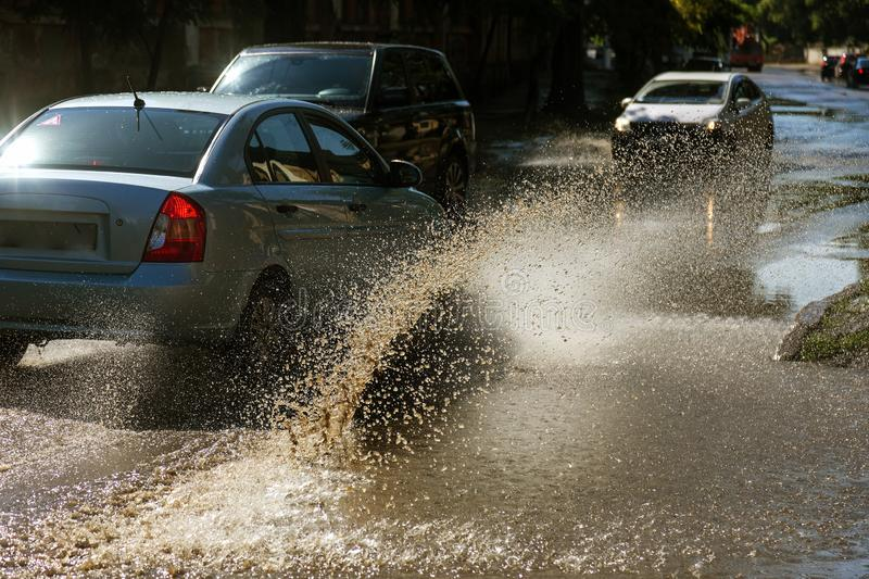 Driving cars on a flooded road during floods caused by rain storms. Cars float on water, flooding streets. Splash on the machine. Flooded city road with a big stock images