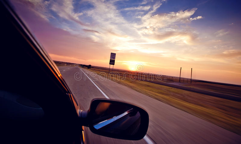 Driving in convertible through highway at sundown royalty free stock images
