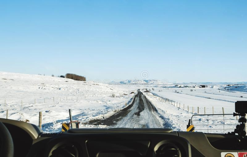 Driving on the country road in winter. Looking through car front windscreen, frozen road with snow covered and clear blue sky in I. Driving on the country road stock photo