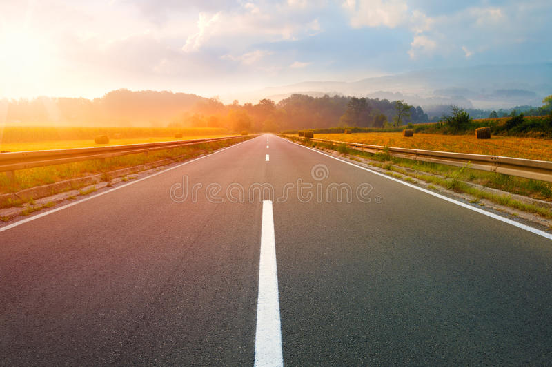 Driving on an empty road at dawn stock images