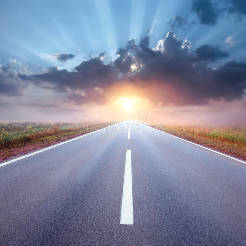 Driving on an empty road towards the rising sun royalty free stock photo