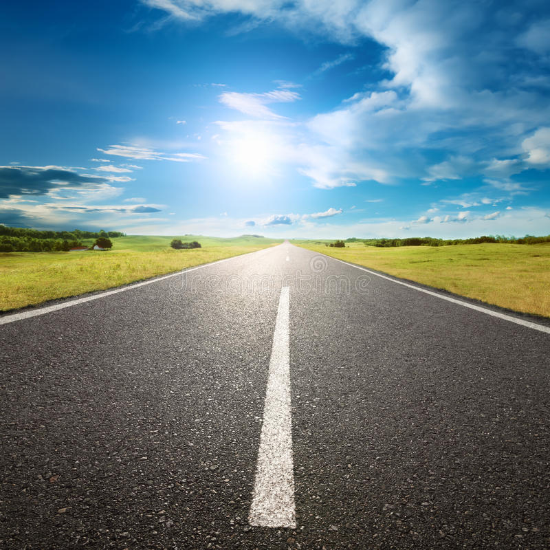 Driving on empty road towards the sun royalty free stock photos