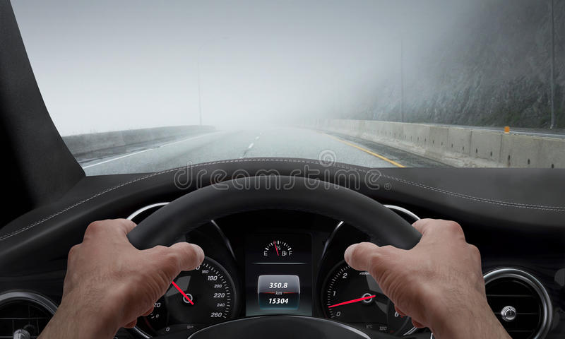 Driving in fog weather. View from the driver angle while hands on the wheel.  stock photo