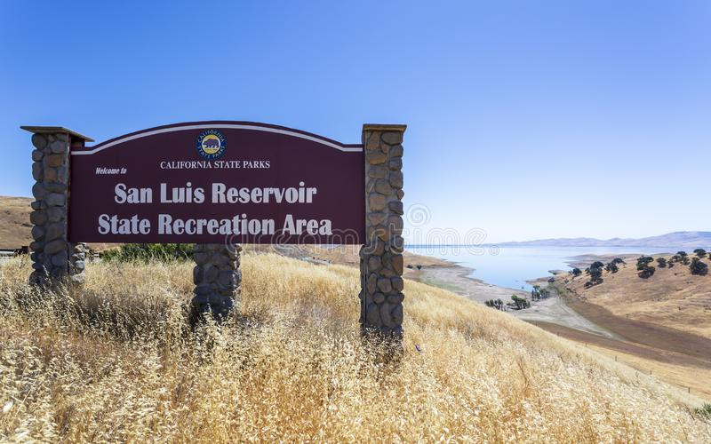 Driving through the golden hills of California; the San Luis Reservoir State Recreation area sign and dam on the right stock images