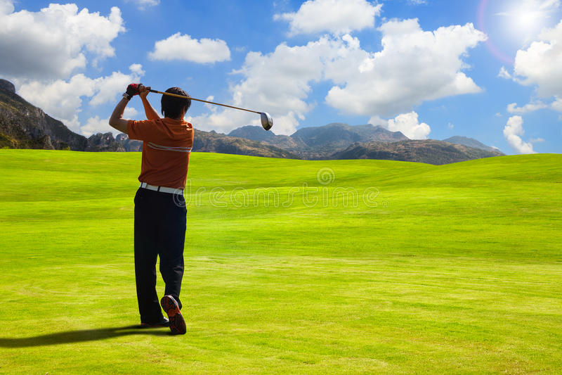 Driving. Golfer driving golf ball on beautiful golf course with clear blue sky in the mountains royalty free stock images