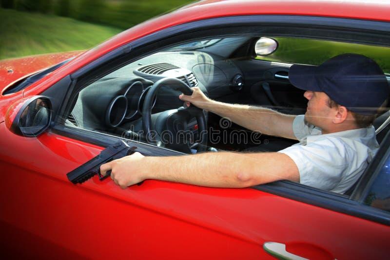 Driving with gun. Man holding gun driving red car stock photos