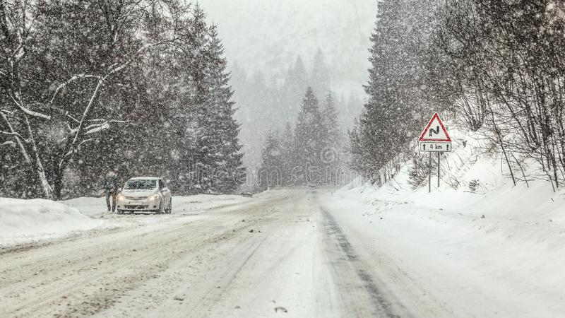 Driving through heavy snowstorm blizzard at forest road, warning curves ahead sign right, and anonymous man with his car stopped stock images