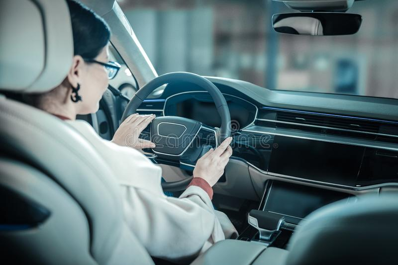 Businesswoman wearing beige coat driving home from work stock photo