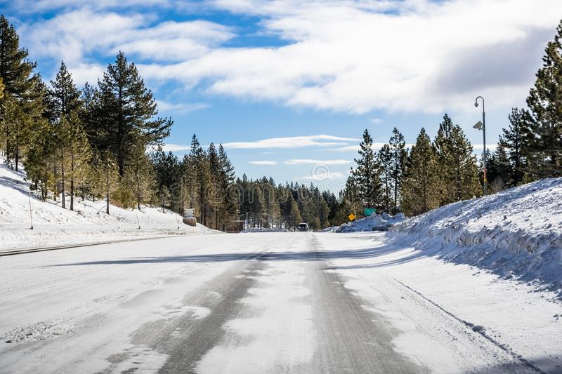 Driving on an ice and snow covered road through the Sierra mountains on a sunny day, Nevada stock photo