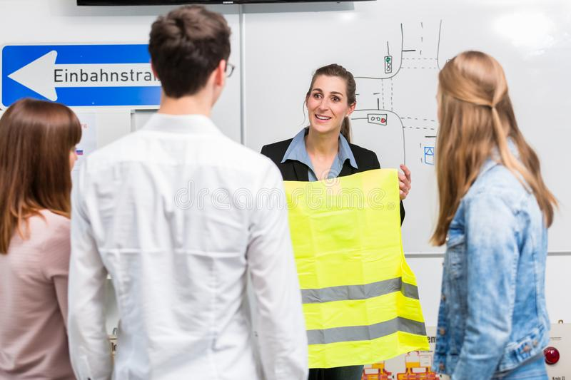 Driving instructor explain the importance of a safety vest stock photography