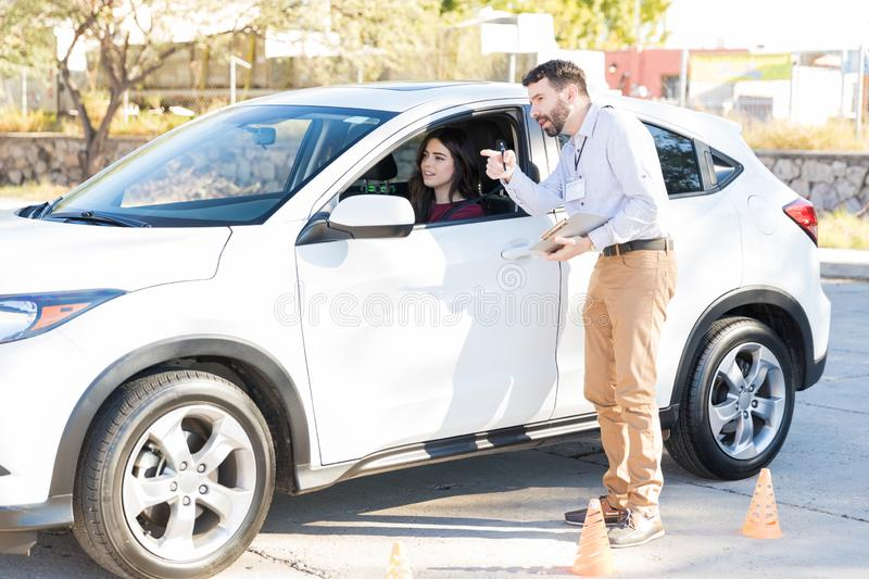 Auto Trainer And Student Communicating During Driving Lessons. Driving instructor explaining directions to women during driving class royalty free stock photo