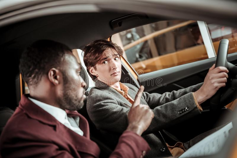Driving instructor explaining young student important rules. Important rules. Bearded professional driving instructor explaining young student important rules royalty free stock photos