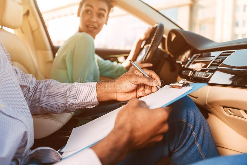 Driving Instructor Writing Down Results Of Exam stock images
