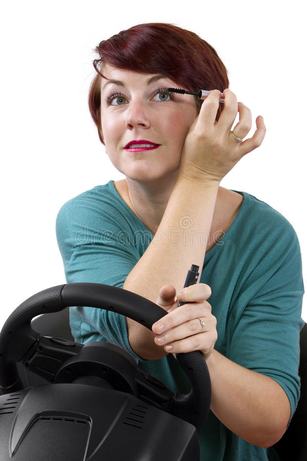 Driving and Late. Young red head woman applying make up while driving stock photo