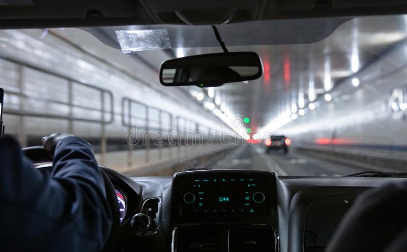 Driving in Lincoln tunnel, New York. Close up view on cab driver hand and dashboard. Lincoln tunnel, New York. Male taxi cab driver holding the steering wheel royalty free stock image