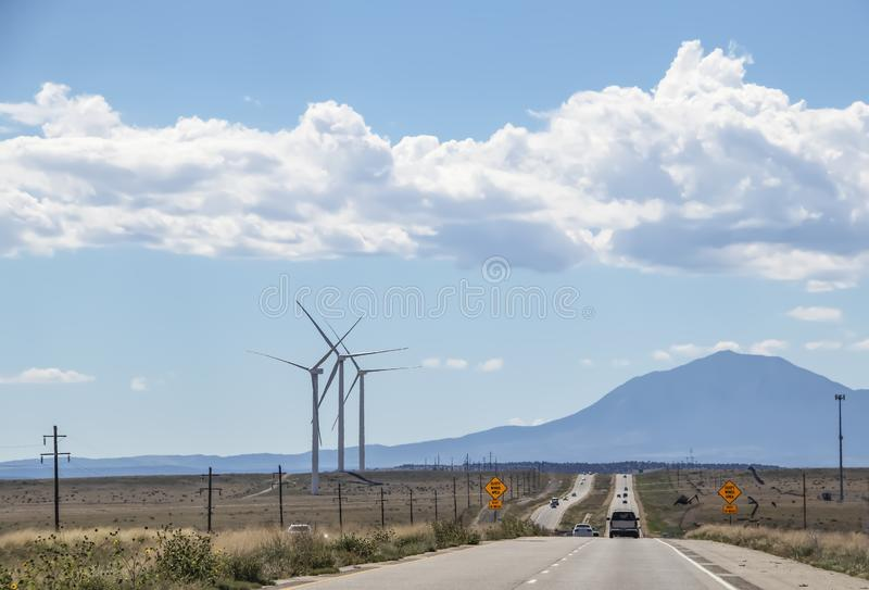 Driving on a long straight road with heat shimmer toward mountains - wind turbines on one side and signs that say Gusty Winds Area. In Southern Colorado USA stock image