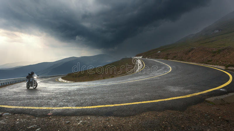 Driving a motorcycle on alpine highway toward the storm royalty free stock photography