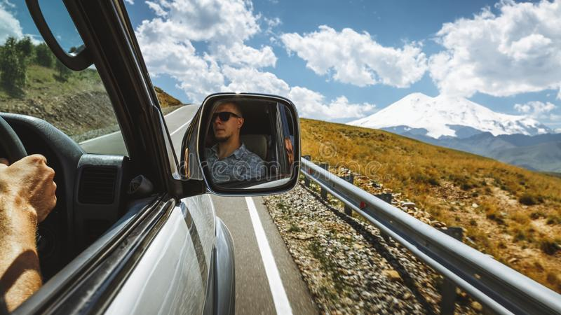 Driving At Mountain Road. Driver In A Car Side Mirror. Road Trip Journey Lifestyle Concept. Driver enjoy view on mountain road. Man face is reflected in side royalty free stock photography