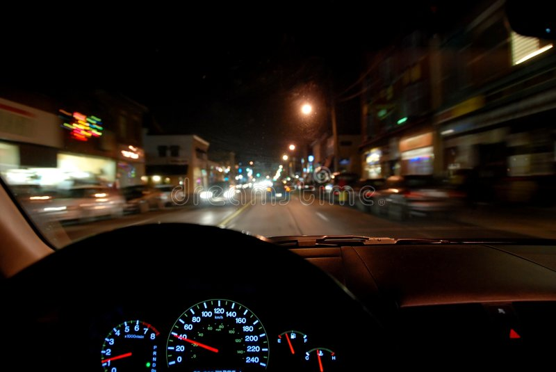 Driving at night. View from inside a car driving at night. sharp dashboard, motion blur outside