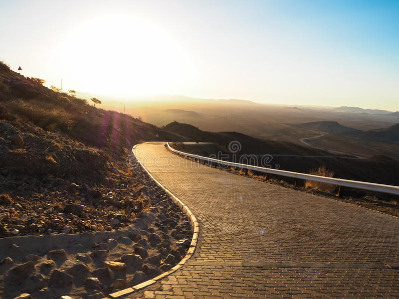 Driving offroad car on adventure road trip through proper block paved curved road among dried desert and rock mountain landscape. To dusty vast horizon on royalty free stock images