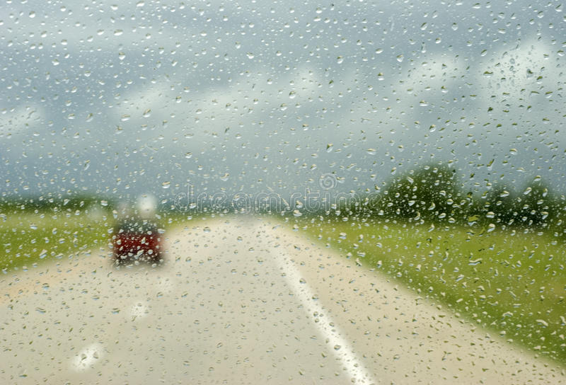 Driving in a Rain Storm. Image of rain drops hitting vehicle windshield during a heavy rain storm royalty free stock photography