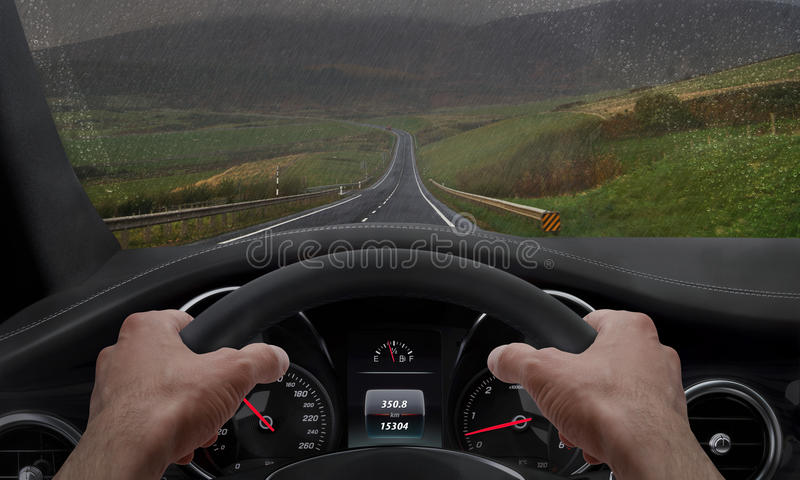 Driving in rainy weather. View from the driver angle while hands on the wheel. Rain splashed windshield.  royalty free stock image