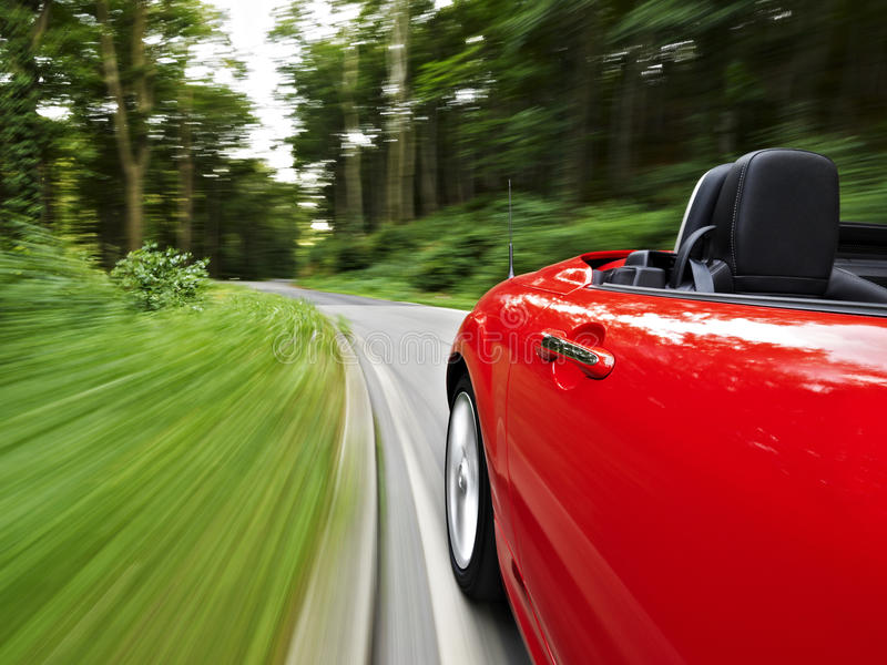 Driving in a roadster. Driving shot of a red roadster on the road in the woods royalty free stock photography