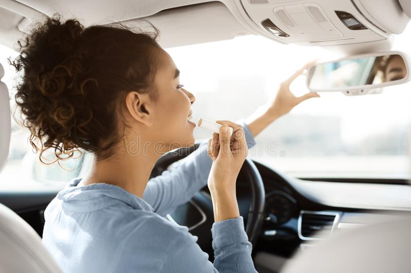 Driving safety concept. Afro woman doing makeup in car stock photos