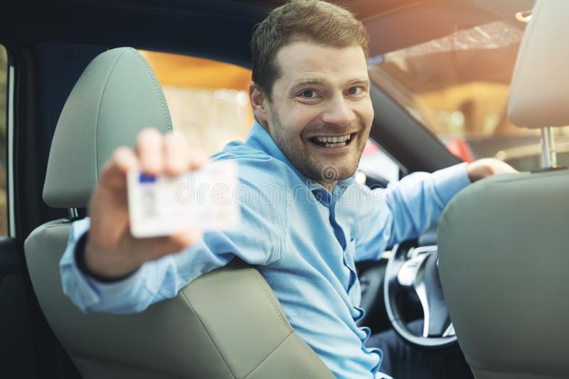 Driving school - man sitting inside the car and showing his driver license stock photo