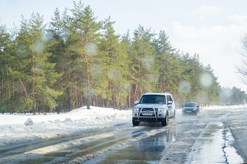 Driving on a snowy road in winter or early spring. View from the car window on the road with melting snow on it. Severodonetsk, Ukraine - March 4th, 2018: View stock photography