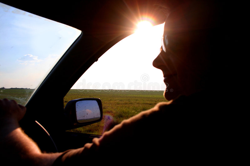 Driving on a sunny day. A closeup of a male driver, cruising along along a road out in the countryside. He is cast in shadows as the sun shines brightly from his stock images
