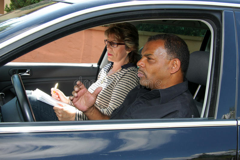 Driving test. A mature African - American man having a driving test and being stressed out by the tester stock image