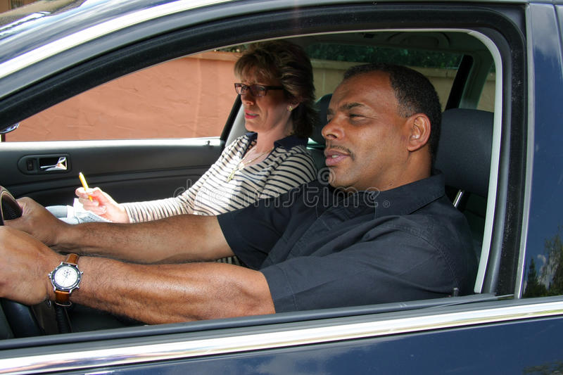Driving test. A mature African - American man having a driving test and being stressed out by the tester stock photos
