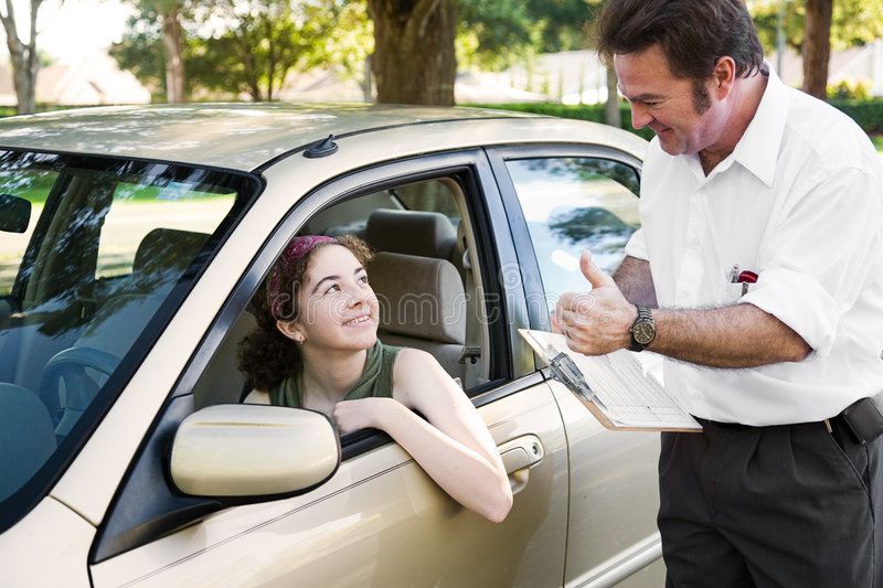 Driving Test - You Passed. Teen girl passes her driving test and gets a thumbs up from her instructor stock photos