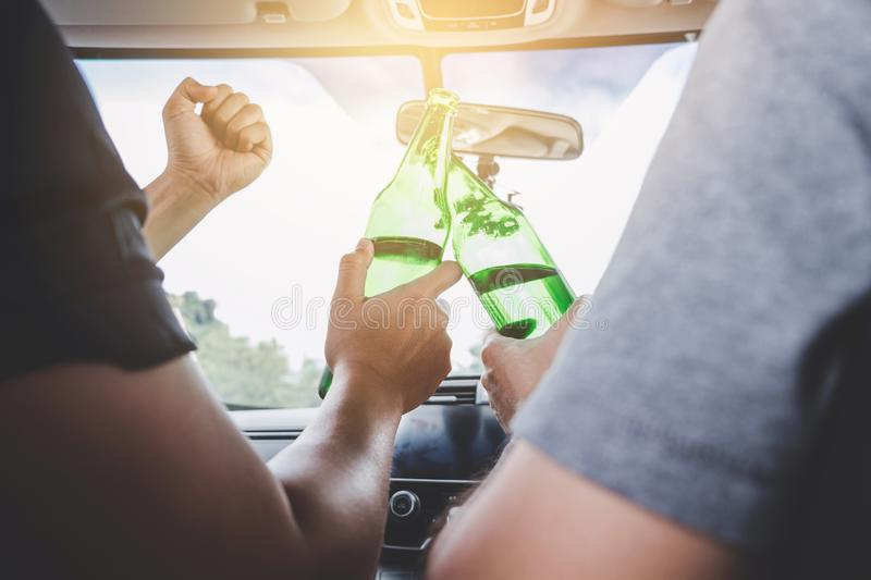 Driving under the influence get into accident, Two asian man drives a car with drunk a bottle of beer alcohol behind the steering royalty free stock photos