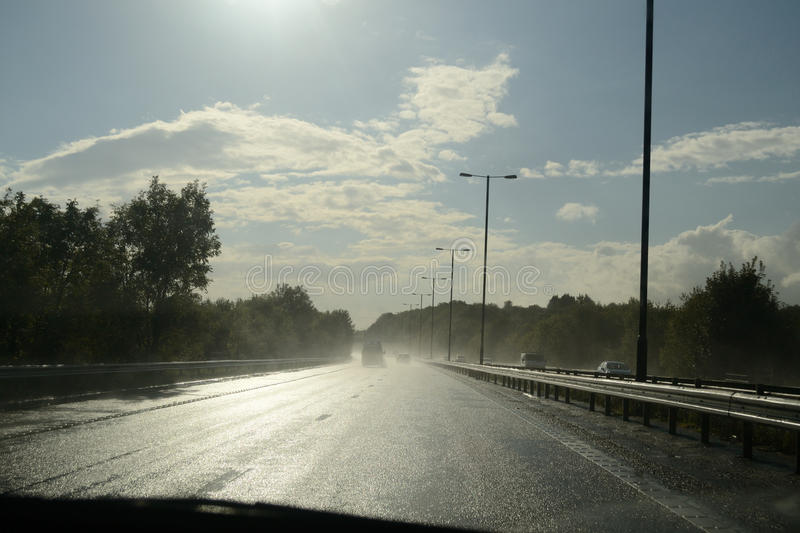 Driving in wet conditions. Abstract of dangerous situation when sun reflects off water royalty free stock photo