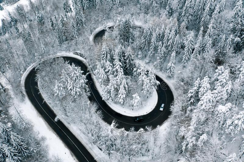Driving on winter roads trough a forest winding road in the mountains stock photo
