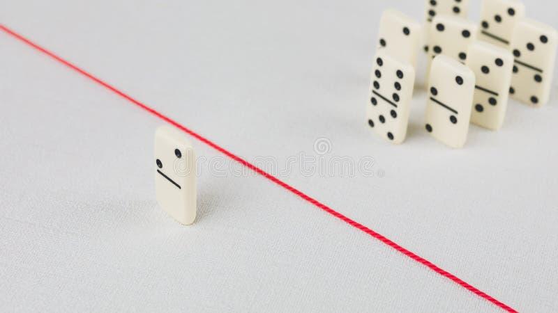 Drivit ut från gruppen som är oförmögen att korsa röda linjen som avskiljer dem Plats med gruppen av dominobricka Begrepp av royaltyfri foto
