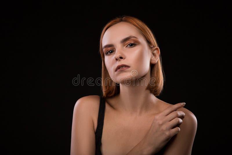 Droevig blond vrouwenportret tegen zwarte achtergrond stock foto