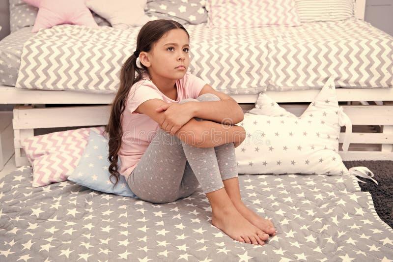 Droevig concept Droevig meisje Het droevige kind zit op bed Droevig jong geitje in slaapkamer thuis Ik wil spelen royalty-vrije stock foto's