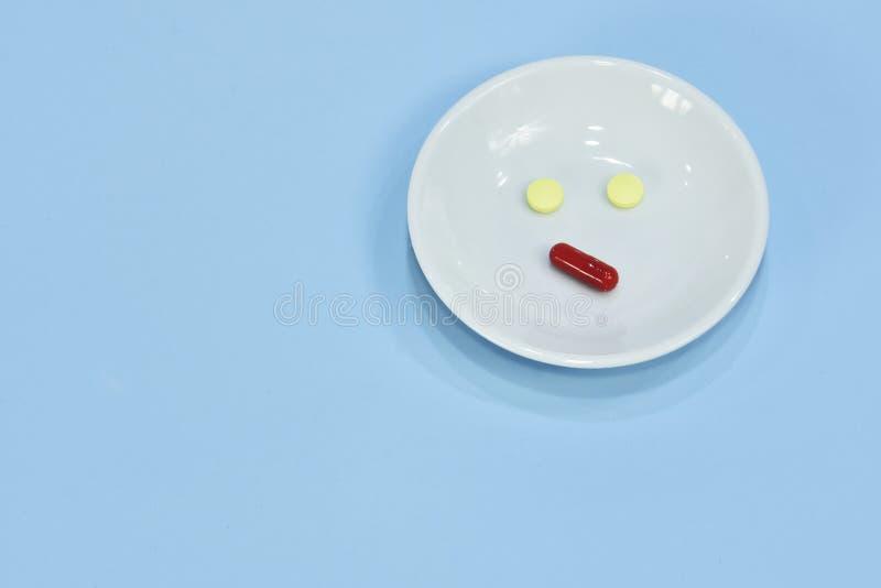 Droevig die gezicht van geneeskunde wordt gemaakt de tabletten van het pijnmedicijn Geassorteerde farmaceutische pillen, tablette stock afbeelding