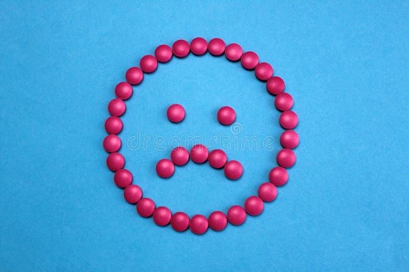 Droevig die gezicht van roze pillen op blauwe achtergrond wordt opgemaakt stock foto's