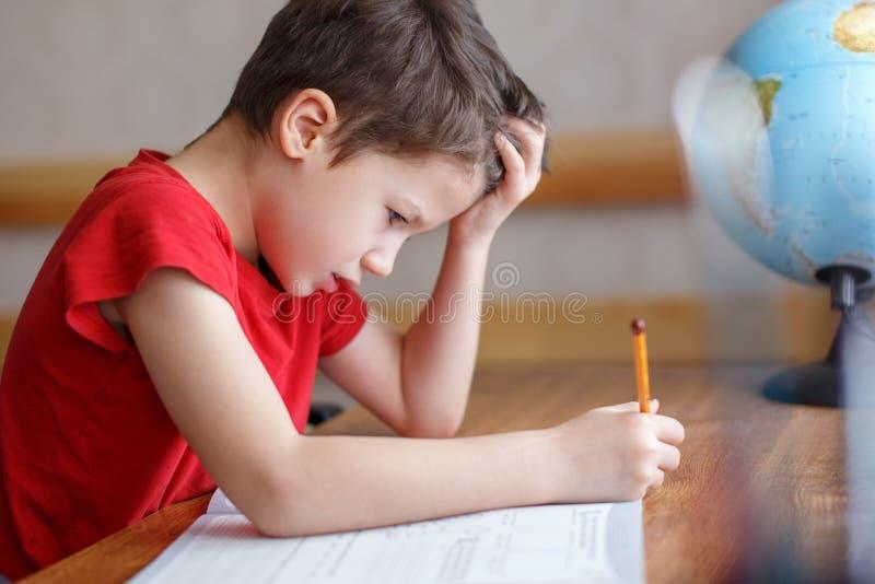 Droevig drukte weinig jongen terwijl het doen van thuiswerk in royalty-vrije stock foto's