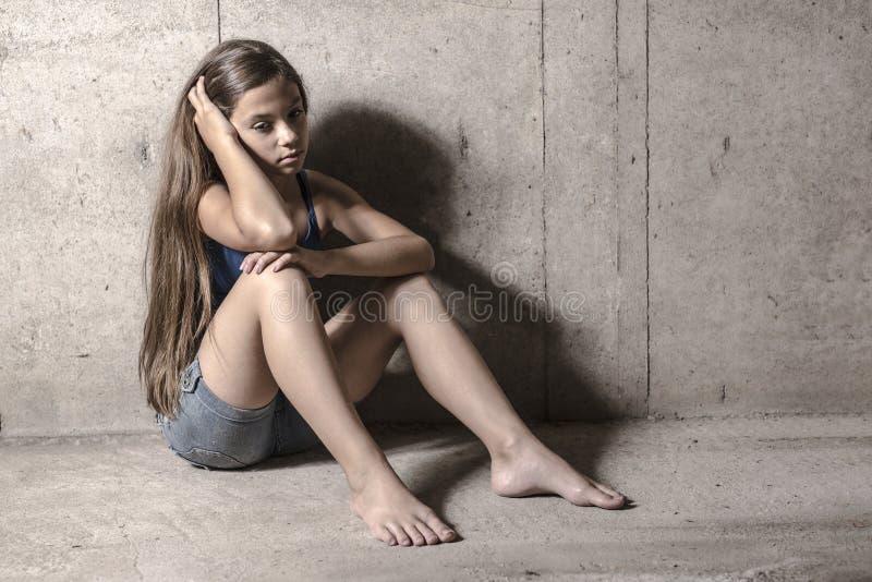 Droevig en eenzaam meisje naast muur royalty-vrije stock afbeeldingen