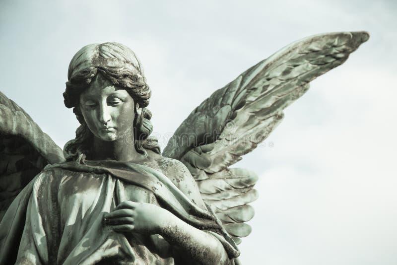 Droevig engelenbeeldhouwwerk met open lange vleugels over het kader desaturated tegen een heldere witte hemel Het droevige beeldh stock foto
