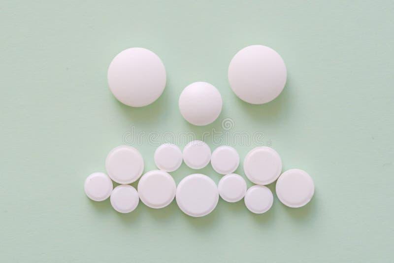 Droevig geduldig die gezicht van witte ronde pillen op groen wordt gemaakt stock afbeeldingen