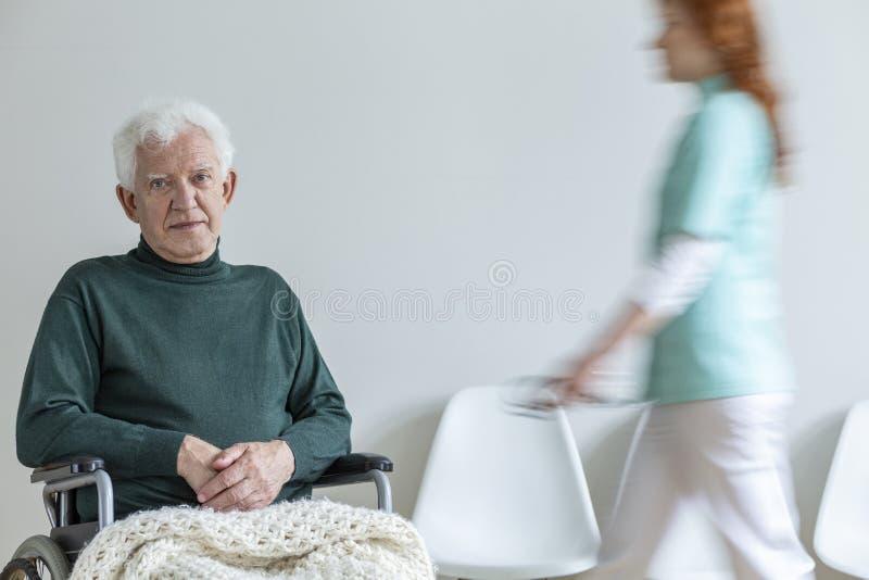 Droevig gehandicapt bejaarde in groene sweater in het ziekenhuis en een onduidelijk beeld stock foto's