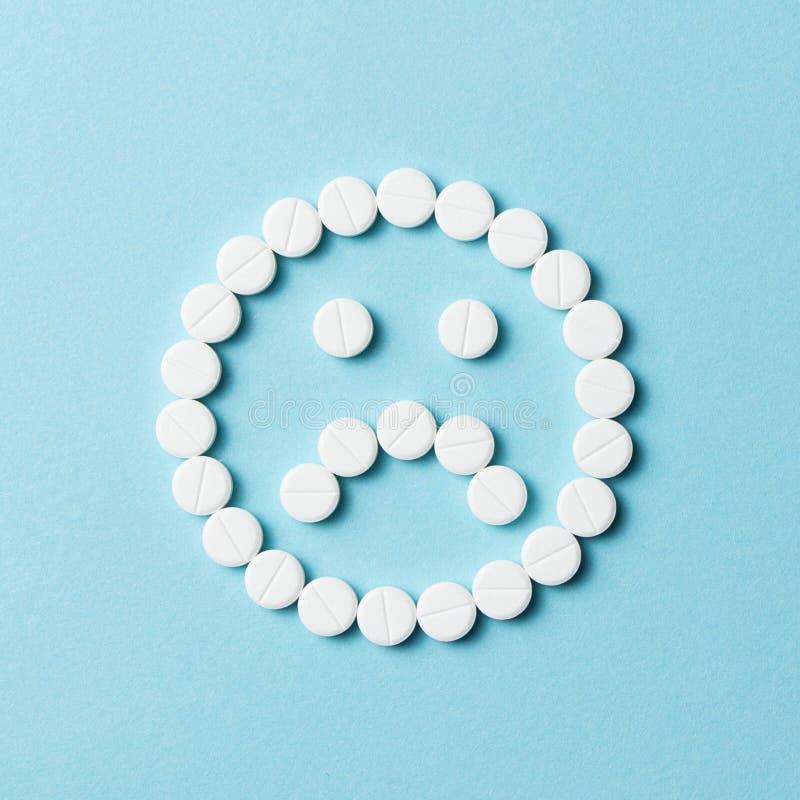 Droevig gezicht met witte pillen stock fotografie